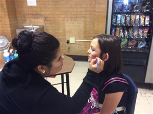 teen painting girl's face