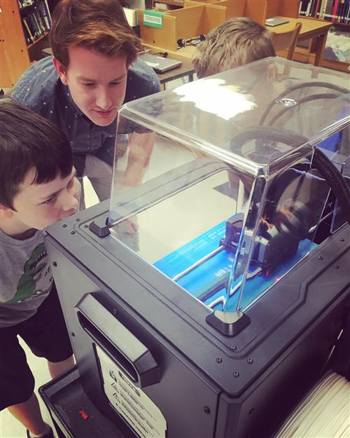 Nick Baker helps students with the 3D Printer